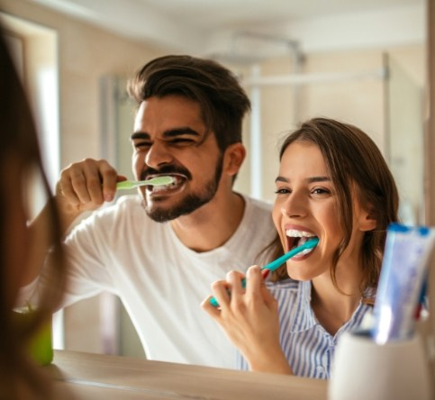 Man and woman brushing teeth to prevent dental emergencies