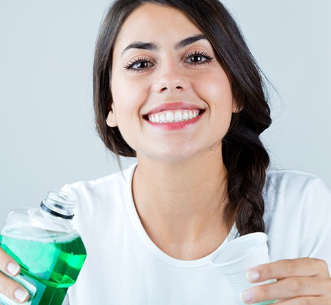 Woman using mouthwash to combat bad breath